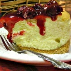 Tall New York Cheesecake on a white plate with a fork