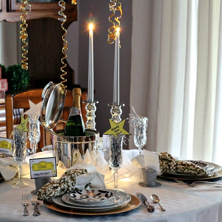 New Years Eve Tablescape with Black, Gold and Silver is timeless elegance. A centerpiece of silver on sheer fabric is lit from underneath adding a gorgeous glow. Free printable name tags and Happy New Year Stars available on the website!