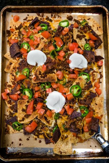Ultimate Beef Nachos are oven crispy tortilla chips drenched in melted cheese, spicy meat and peppers. Perfect for game day, parties and a sheet pan dinner. #mustlovehomecooking