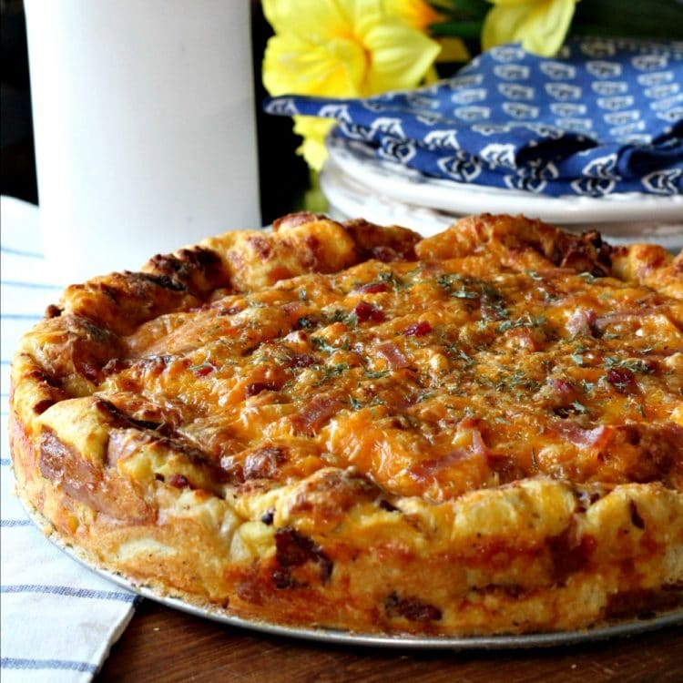 Cheddar Bacon Strata is a savory bread pudding/cake made with just 5 ingredients. Eggs, Bacon, cheese, bread and milk are what you need to make this delicious and gorgeous Strata. The Strata can be made a day ahead of time too! Click over for the complete recipe and easy instructions.