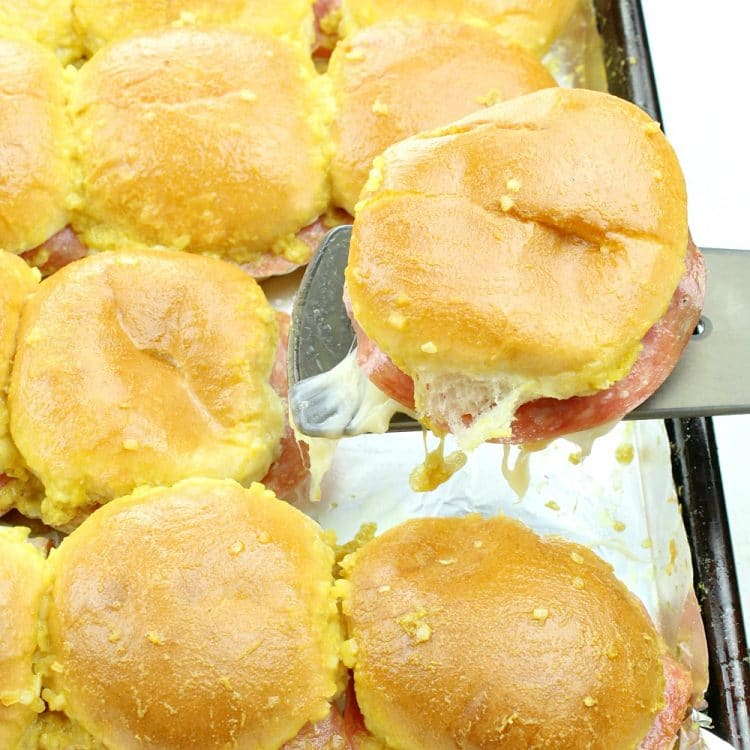 Italian Ham and Cheese Sliders - hot and tangy little sandwiches that are big on flavor.  Savory ham, spicy salami, velvety swiss cheese and a zippy mustard sauce combine to make an irresistible snack or a meal that everyone will love!