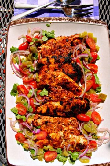 Harissa Chicken are grilled chicken breasts that have been marinated with a harissa rub of paprika, chipotle chilies, adobo sauce and cumin then served with a refreshing cilantro salad. Great alone or used as taco filling or the base for spicy chicken salad!
