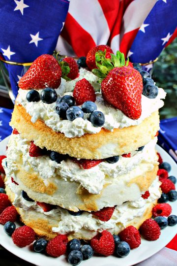 Patriotic Angel Food Cake is layers of fluffy angel food cake, stuffed with a cream cheese filling and then fruit mounded in the layers and on top. A perfect summer dessert! #mustlovehomecooking