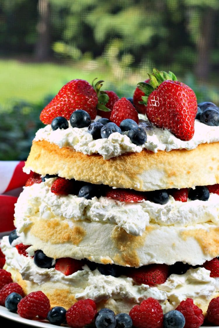 Patriotic Angel Food Cake is layers of fluffy cake, stuffed with a cream cheese filling and then fruit mounded in the layers and on top. A perfect summer dessert!