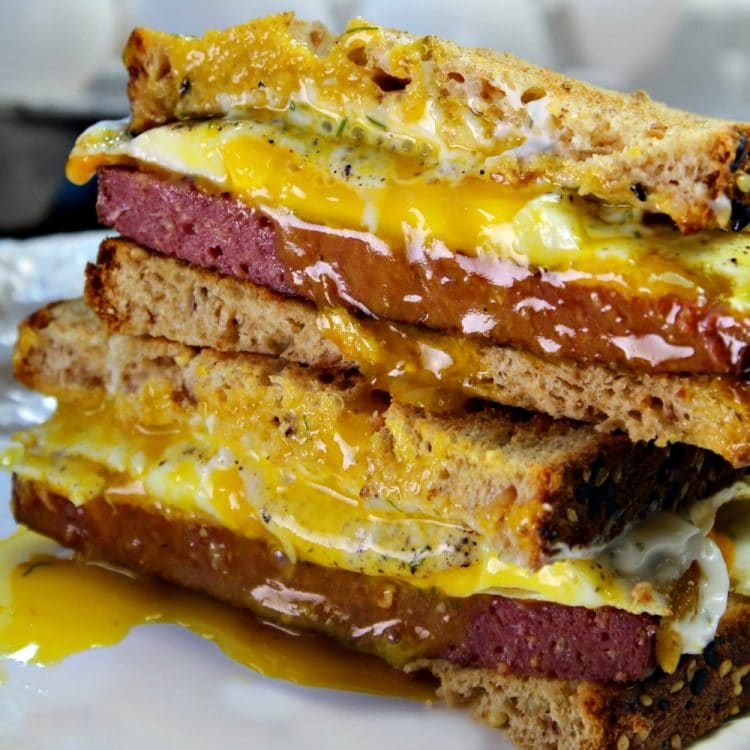 A Buckeye Breakfast Sandwich is a thick slab of Lebanon Bologna, aged cheddar cheese, and a fried egg served on toasted wheat bread that has been slathered with dill mayonnaise - a tasty family favorite and quick recipe that takes less than 10 minutes!