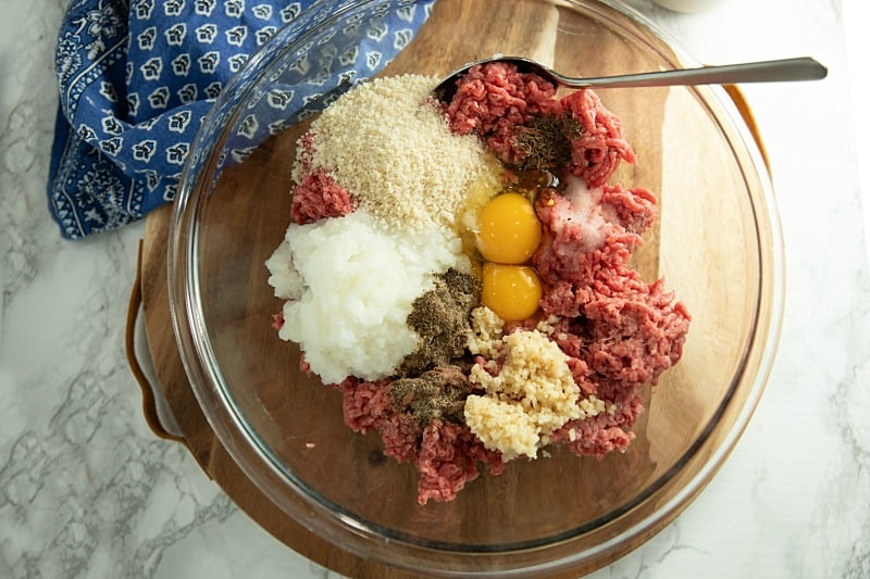 Ingredients for meatballs in glass mixing bowl