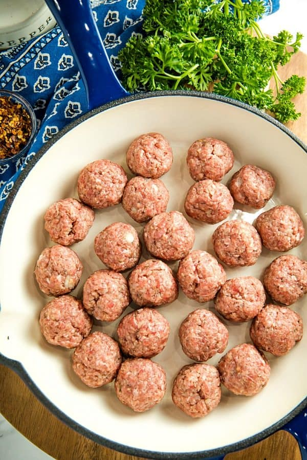 Seasoned rolled meatballs in blue skillet ready for cooking