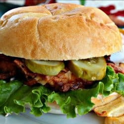 Spicy Fried Chicken Sandwich is a marinated chicken thigh that has been fried to golden and crunchy perfection. It is served on bun with a thick sliced pickle and slathered with buttermilk chili sauce. The secret is in the simple marinade, leaving the chicken moist with melt-in-your-mouth flavor.