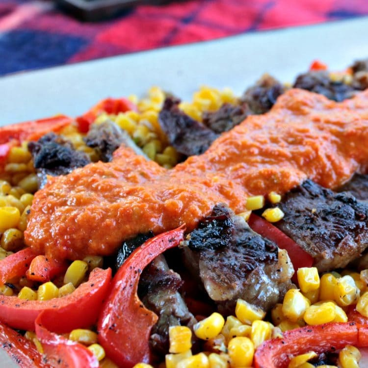 Skirt Steak with Red Pepper Puree is marinated then grilled skirt steak drenched in a smooth and flavorful red pepper puree. Served with pan fried peppers, corn and red onion.