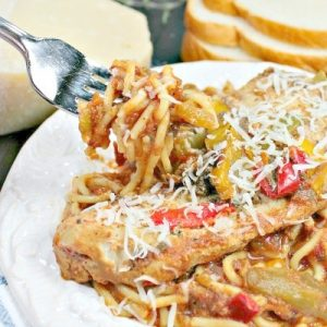 Easy Slow Cooker Tuscan Chicken is tender chicken, seasoned with peppers and Italian herbs, served on a bed of pasta!