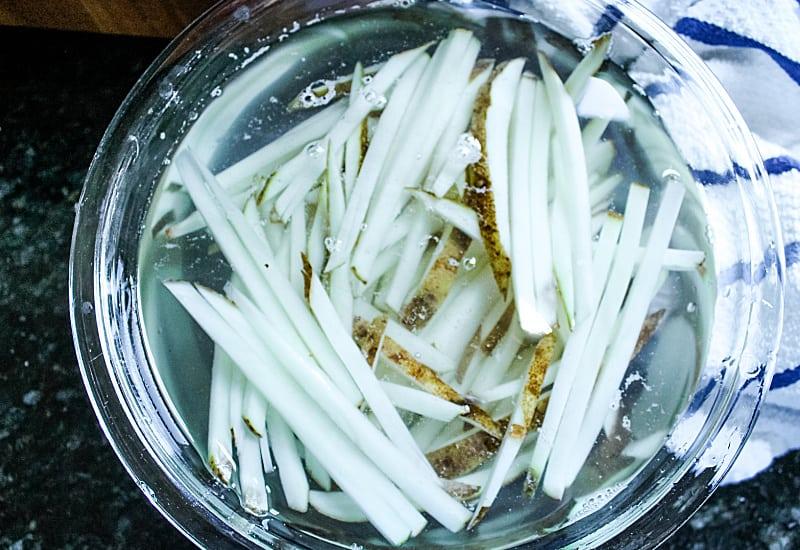 cut potatoes soaking in glass mixing bowl of water