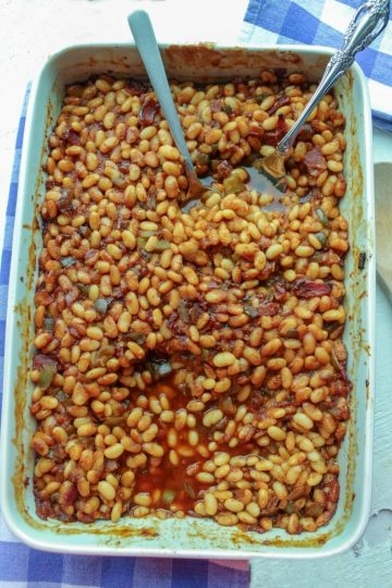 From Scratch Cola Baked beans in white baking dish with spoon