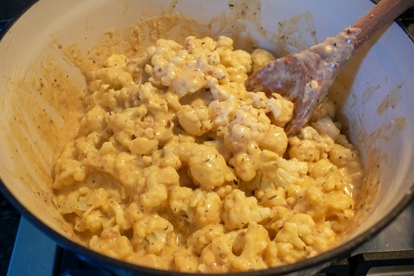 cauliflower in dutch oven covered with melted cheese