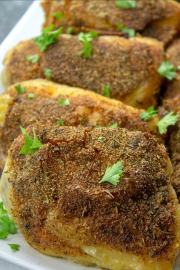 crispy oven baked chicken thigh on white platter with parsley