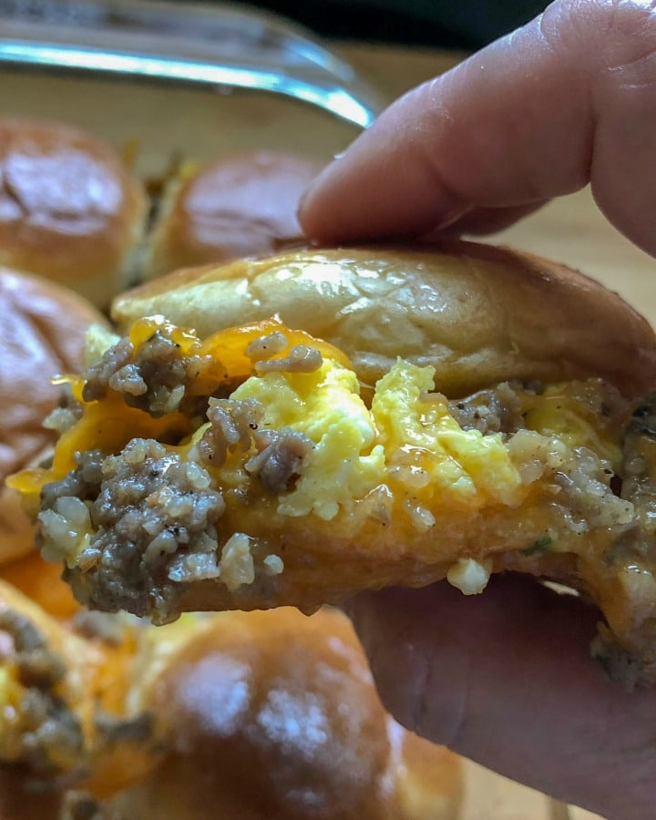 egg sausage breakfast slider held in hand