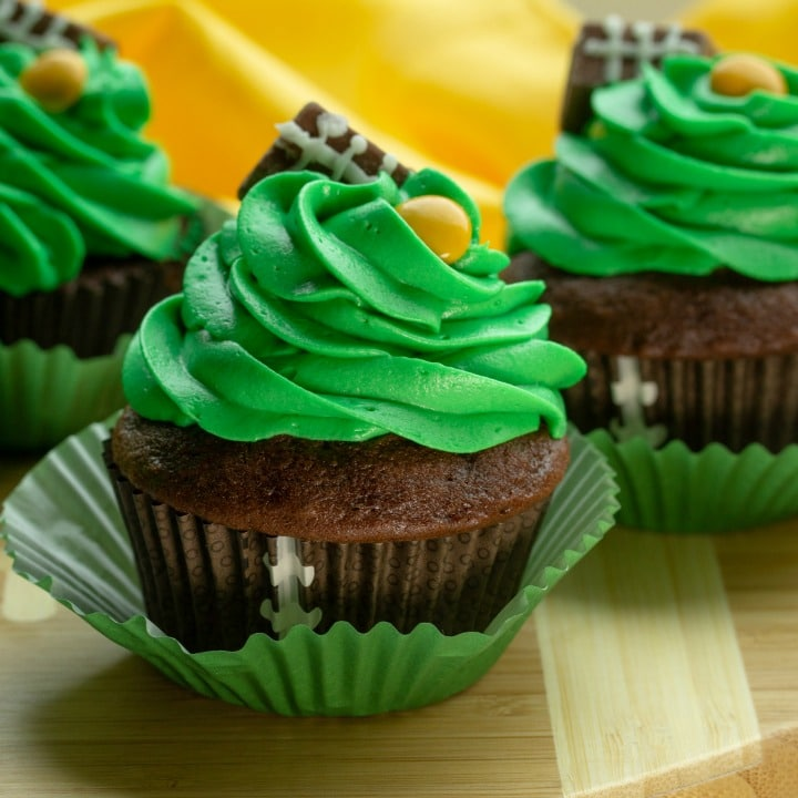 Easy Candy Football Cupcakes are chocolate cake, topped with rich buttercream frosting. Decorated with candies, these cupcakes are perfect for game day parties and tailgating!