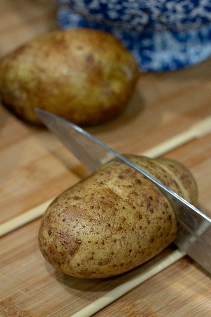 slicing hasselback potatoes with knife and chopsticks