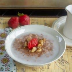 Easy Slow Cooker Strawberry Honey Oatmeal in white bowl set for breakfast
