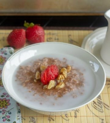 Easy Slow Cooker Strawberry Honey Oatmeal in white bowl set for breakfast