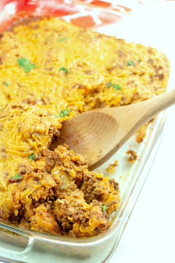 Taco Biscuit Casserole being served with wooden spoon