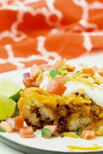 Taco Biscuit Casserole served on white plate with sour cream and pico de gallo