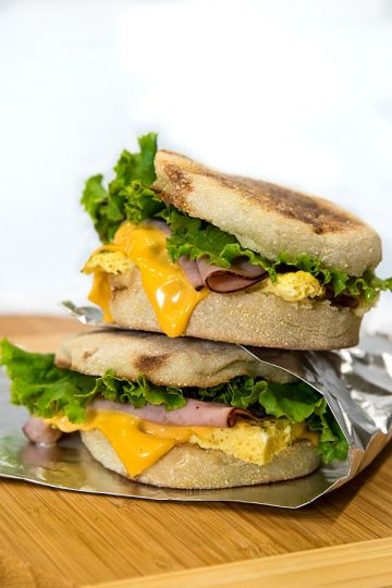 Easy make ahead freezer breakfast sandwiches are ready for a start the day meal on-the-go. Prep a batch with herb seasoned eggs, ham and sliced cheese in under 25 minutes!