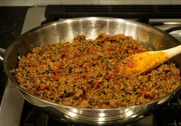 Ground beef with tomatoes and chilies cooking in skillet