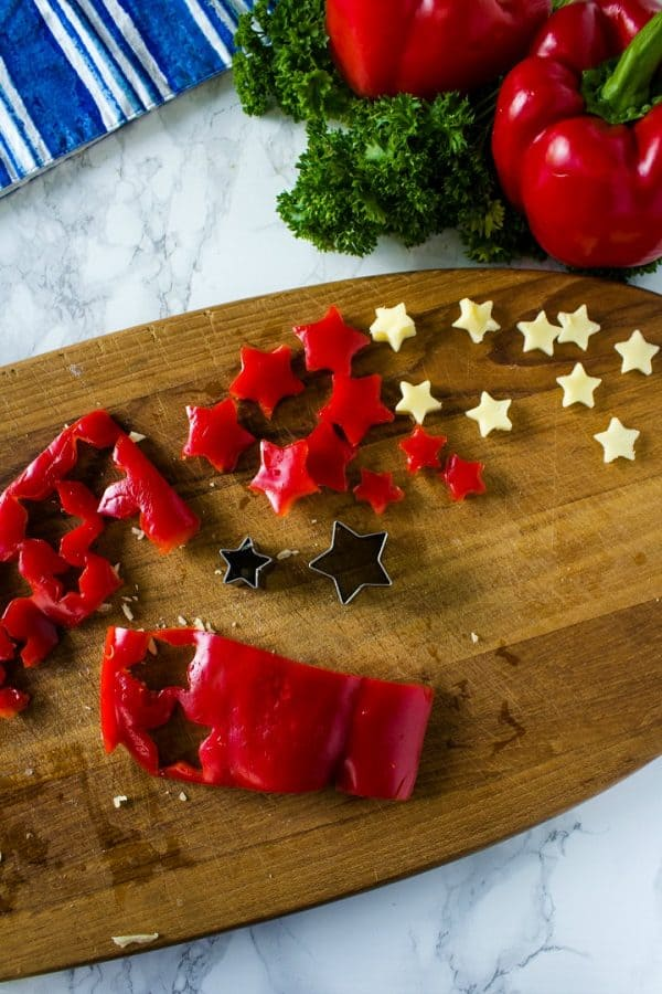mini red pepper and cheese star cutouts to decorate cheese ball