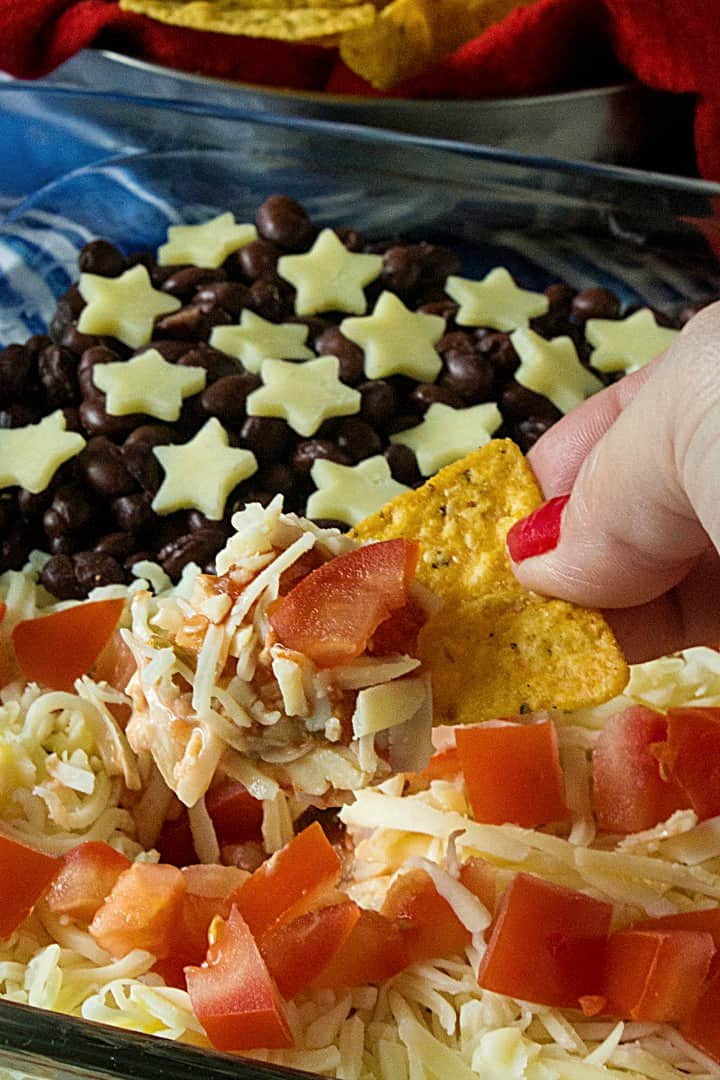 Patriotic Layered Party Dip is a huge hit at summer parties. Seasoned sour cream, black and refried beans, cheese and tomatoes are layered into a zesty 10 minute dip everyone will love! #mustlovehomecooking