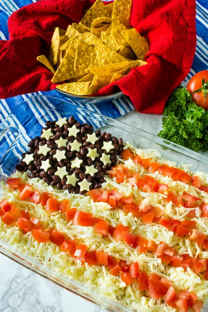 Patriotic Layered Party Dip is a huge hit at any summer party. Layer taco sour cream, beans, cheese and tomatoes for a quick, zesty dip!