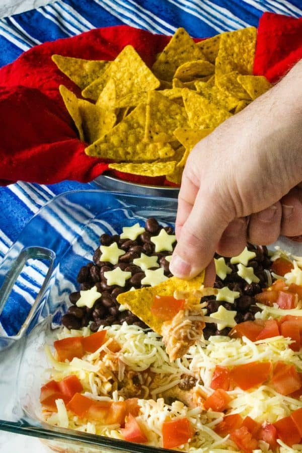 Patriotic Layered Party Dip is a huge hit at summer parties. Seasoned sour cream, black and refried beans, cheese and tomatoes are layered into a zesty dip everyone will love!