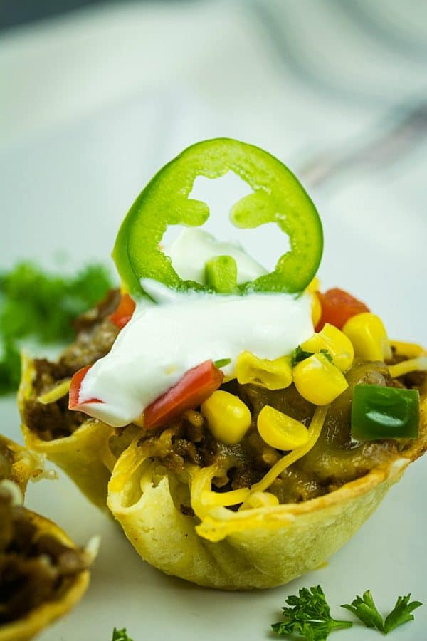 Tortilla taco cups are fun appetizers and a tasty twist on taco night. The layers of seasoned beef and melting cheese are heated in mini corn tortilla cups, then loaded with your favorite taco toppings!