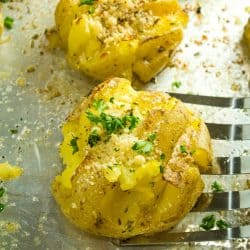 Garlic Herb Smashed Potatoes! Boiled potatoes smashed in their skins, then drizzled with butter, herbs and garlic and broiled until crispy brown. Parmesan cheese adds a tangy final touch.