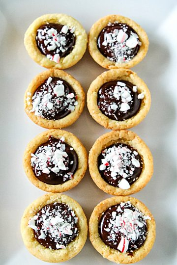 Chocolate Peppermint Sugar Cookie Cups - Tender sugar cookie cups brimming with chocolate ganache filling and crushed peppermint sprinkles! Three holiday favorites in one delicious treat!