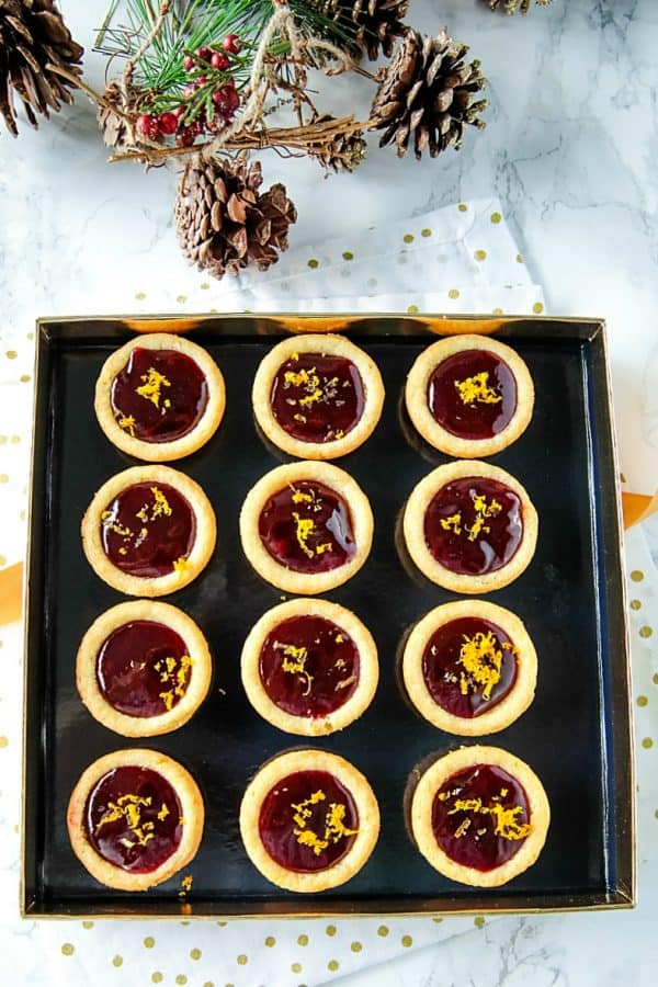 Orange Raspberry Cookie Cups - Buttery orange flavored sugar cookie cups filled with raspberry jam and sprinkled with fresh orange zest. Festive on the cookie tray and easy on the budget.