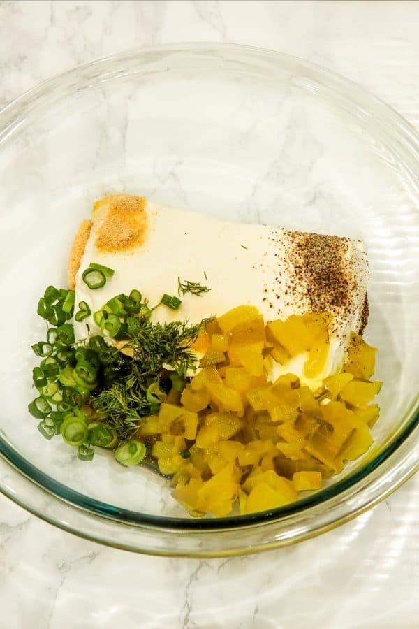 Ingredients to make pickle dip in glass mixing bowl