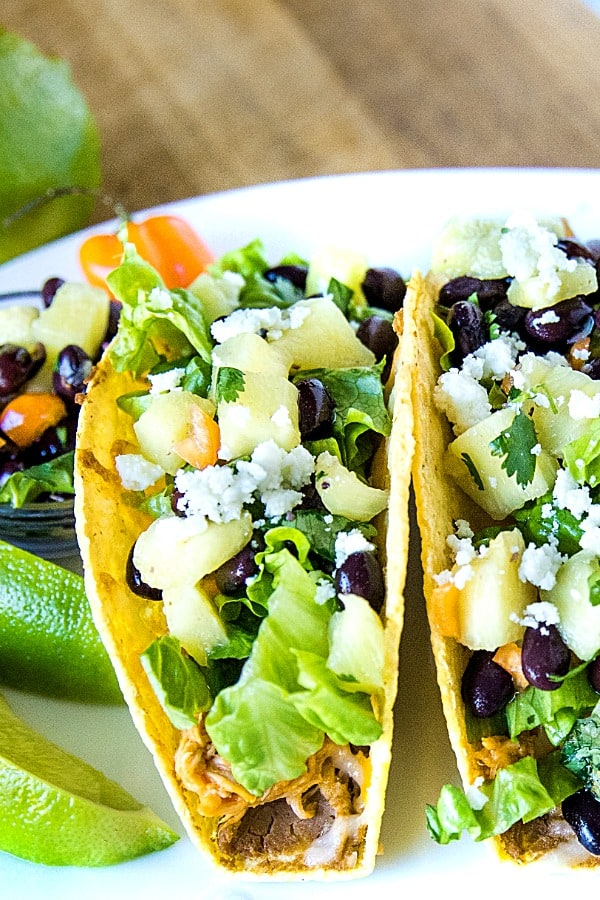 Easy Oven Chicken Tacos are seasoned shredded chicken stuffed into refried bean smeared crunchy shells and topped with cheese. Baked easy in the oven then loaded with spoonfuls of fresh pineapple salsa. #mustlovehomecooing #chickentacos #mexicanfood