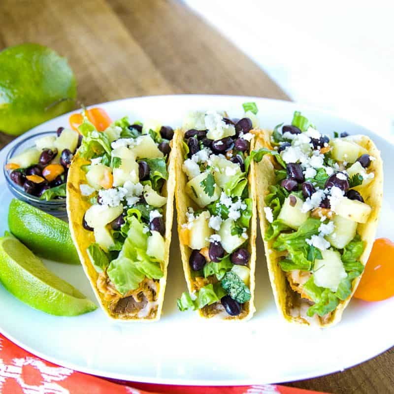 Easy Oven Chicken Tacos are seasoned shredded chicken stuffed into refried bean smeared crunchy shells and topped with cheese. Baked easy in the oven then loaded with spoonfuls of fresh pineapple salsa. #mustlovehomecooking #tacorecipe #mexicanfood