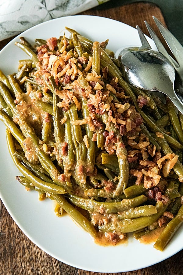 Super tender, loaded with flavor Southern-style green bean recipe with bacon, crispy onions and lots of seasonings. #mustlovehomecooking #slowcookerrecipes #greenbeanrecipe