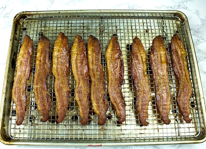 Crispy, smoked bacon cooked perfect every time right in the oven. Big batch bacon cooking with no flipping, no mess and no splatter.