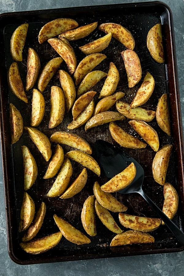 Crispy Roasted Potato Wedges - easy oven baked golden brown potatoes with olive oil, garlic and parmesan cheese. #mustlovehomecooking #ovenpotatorecipes