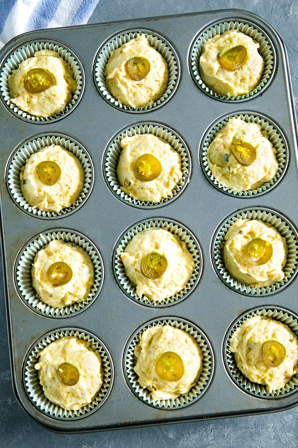 Jiffy cornbread muffins topped with jalapeno slices ready for the oven