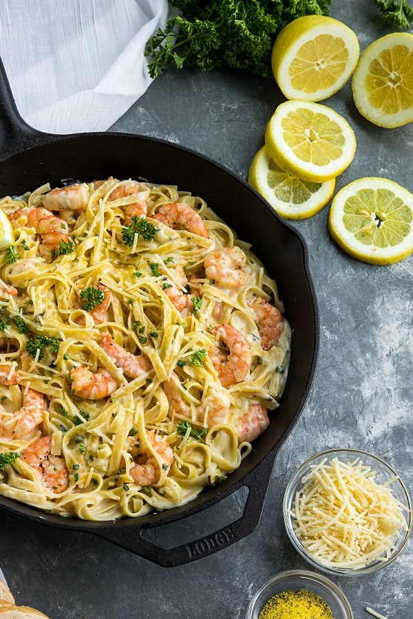 Lemon Pepper Shrimp Alfredo made with lemony seasoned shrimp, fettuccine and an addictive cheesy cream sauce. A busy weeknight favorite! #mustlovehomecooking