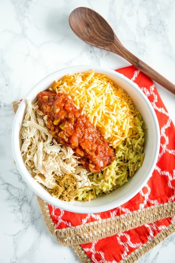 Chicken, rice salsa, cheese and cumin in white mixing bowl