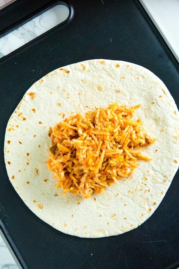 Tortilla with chimichanga filling on black cutting board