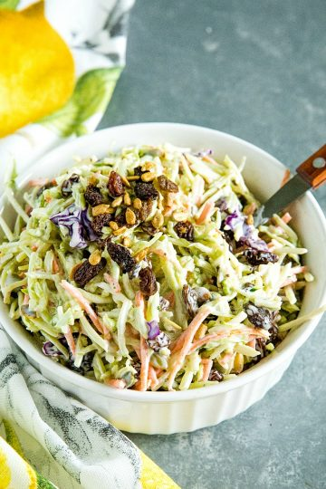 Easy Broccoli Slaw is a healthy, crunchy and sugar free blend of shredded broccoli, raisins and pepitas with an irresistible sweet and sour dressing. #mustlovehomecooking