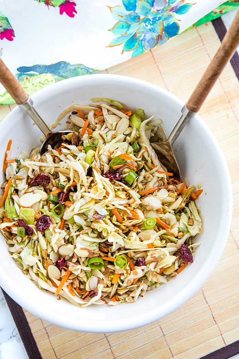 Midwest Cabbage Salad is a cold and crisp side dish made with shredded cabbage, green onions, dried cranberries, almonds. sunflower seeds and sweet dressing is fresh, healthy and stays crunchy in the refrigerator for several days! #mustlovehomecooking