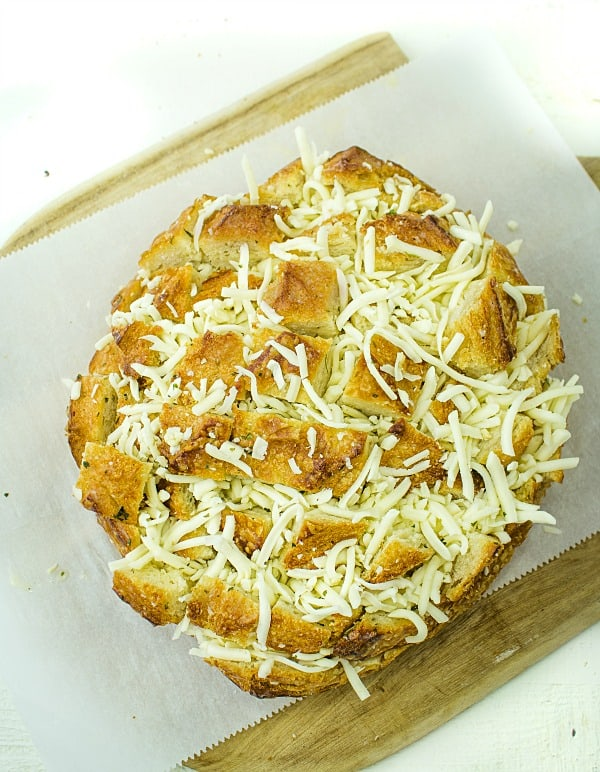 Pull apart three cheese garlic bread is a round sourdough loaf drizzled with garlic butter and stuffed with melting cheese. Crusty, and gooey hot bread made easy in under 30 minutes. #mustlovehomecooking