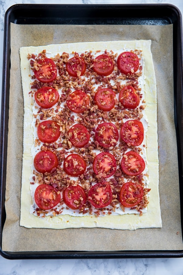puff pastry and tomato tart filling on baking sheet
