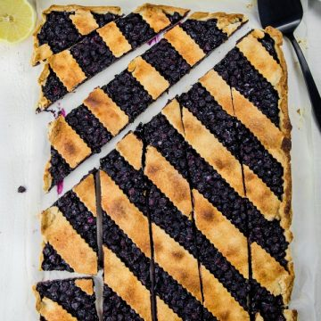 Blueberry Slab Pie is fresh blueberries, cinnamon and lemon juice baking into a buttery and crisp shortbread crust. Easily cuts into bars and feeds a crowd! #mustlovehomecooking